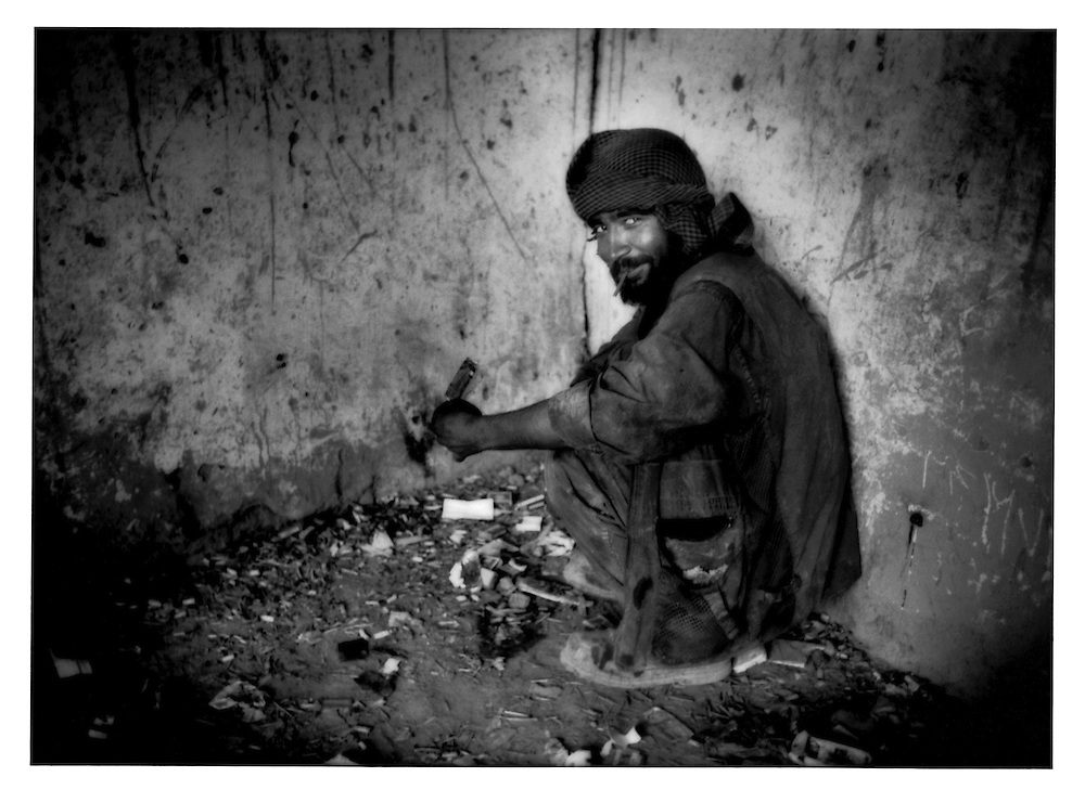Kabuli man displays a hit of heroin on the foil from a cigarette pack as he prepares to smoke it in filthy, abandoned chamber in old city of Kabul, Afghanistan.  There are 40,000 - 50,000 heroin and opium users in Kabul, says Dr. Qureshi, Deputy Director of  Kabul's only gov?t run mental hospital, Psychiatric and Drug Dependency Hospital, Kabul.