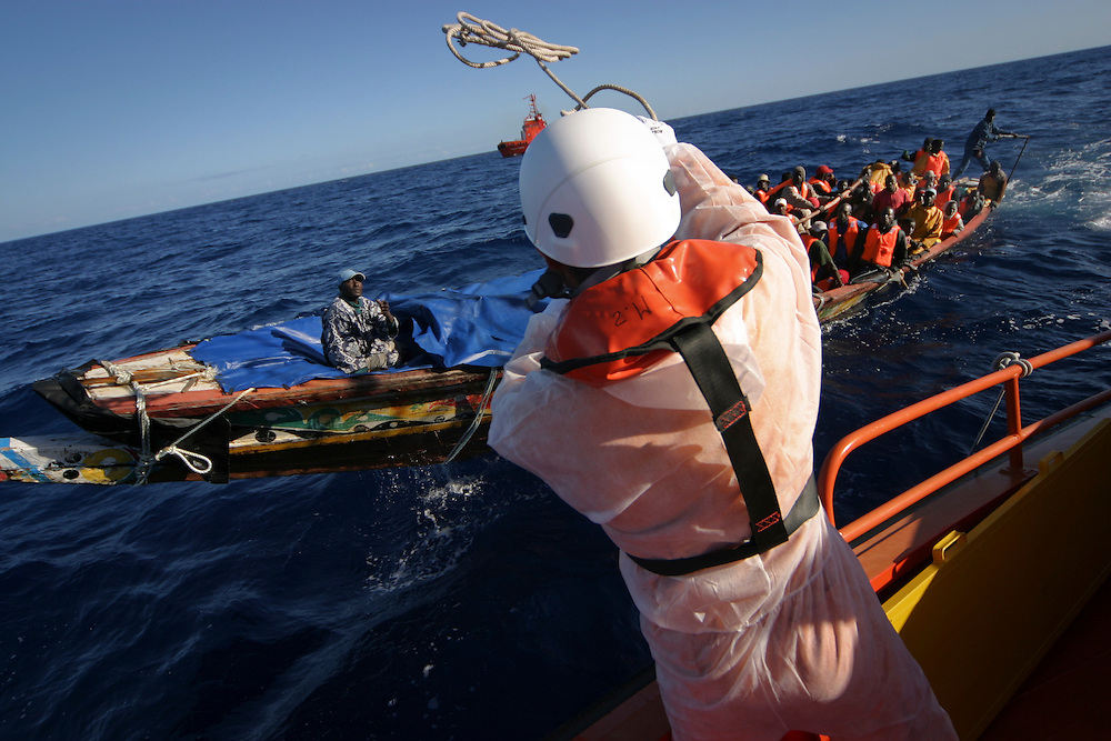 A marine rescue worker throws a rope to the open wooden fishing boat, carrying 47 migrants, intercepted 60 miles away from the coast of Tenerife, in the Canary Islands, Spain, Thursday, June 15, 2006. Thousands of people try to reach Europe through Spain each year, an increasing number of them coming from Mauritania and Moroccan-controlled Western Sahara. Mauritania's Red Crescent says more than 1,000 people have died trying to reach Spain since the beginning of the year.