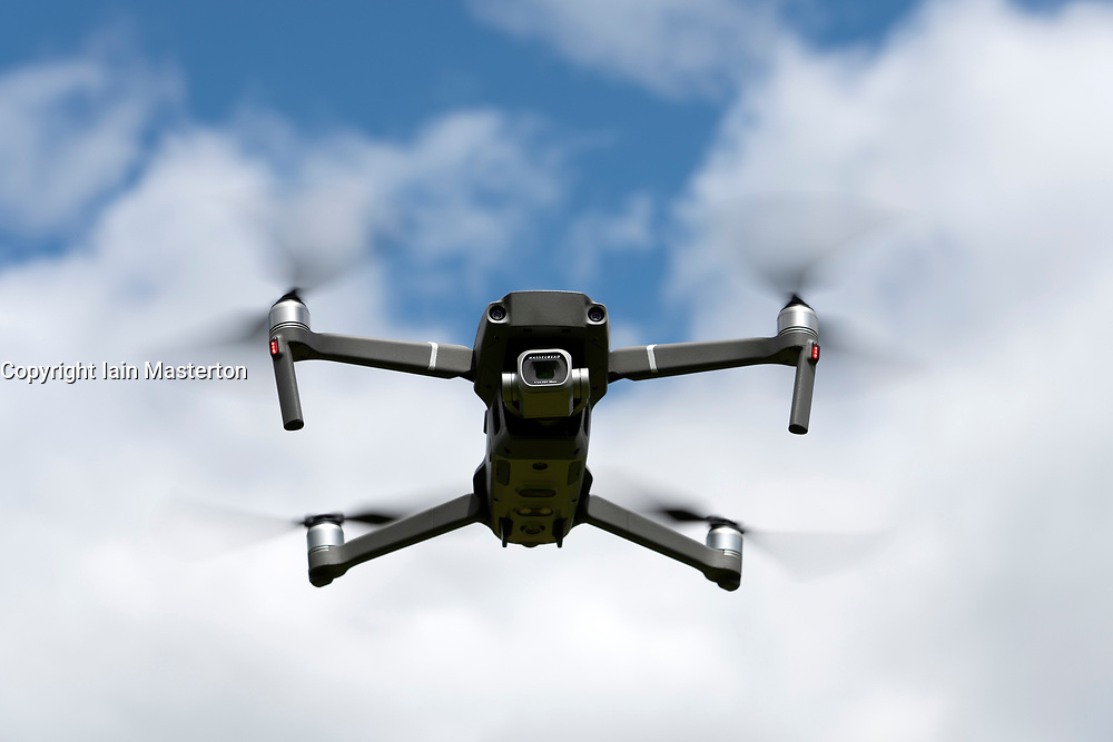 View of modern consumer drone with camera on gimbal in hover mode outdoors