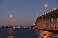 The full moon rises over Virginia Key behind the William M. Powell Bridge. The bridge connects the Florida mainland to Key Biscayne and Virginia Key as part of Miami's Rickenbacker Causeway. The bridge is also effectively the highest hill in South Florida at 80 feet in height.<br />