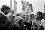 Natural theatre company hold up national no smiling day placards in front of a crowd. Glastonbury 1994