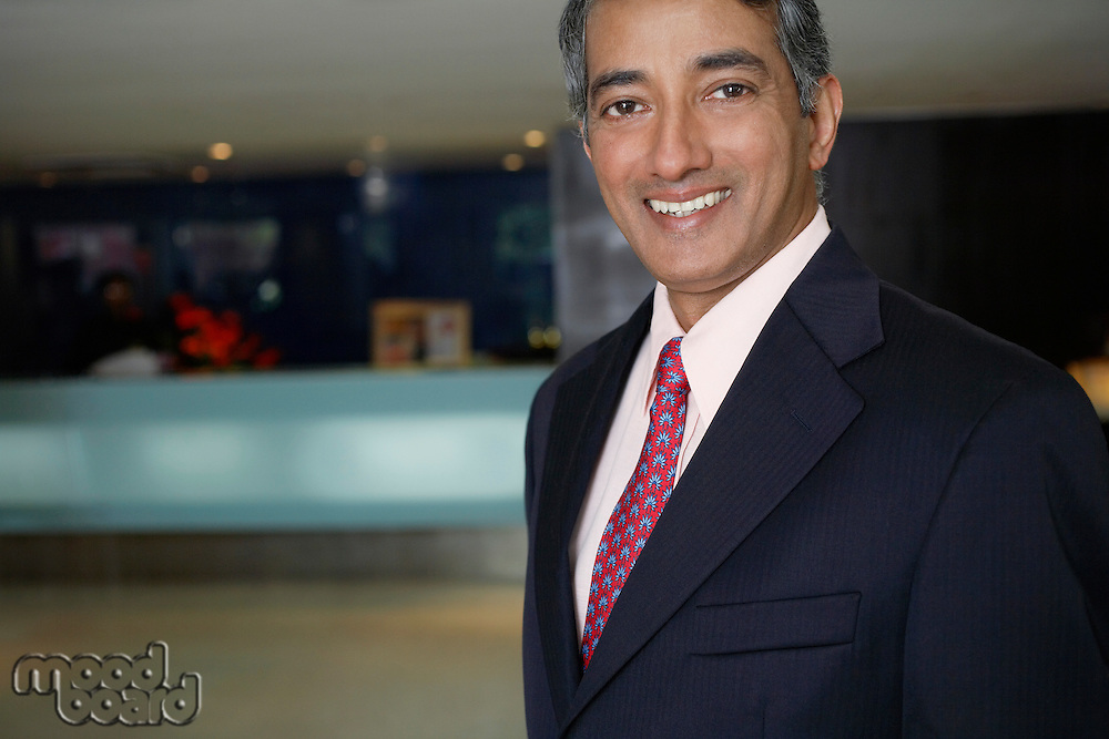 Business man standing in hotel lobby portrait