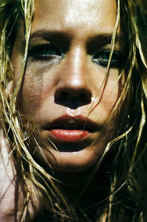 Close up of a young woman's face with long wet hair and red lips