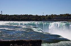 The top or edge of Horseshoe Falls as seen from Terrapin Point on Goat Island.<br /> <br /> Wikipedia:  Niagara Falls is the collective name for three waterfalls that straddle the international border between Canada and the United States; more specifically, between the province of Ontario and the state of New York. They form the southern end of the Niagara Gorge.<br /> From largest to smallest, the three waterfalls are the Horseshoe Falls, the American Falls and the Bridal Veil Falls. The Horseshoe Falls lie on the Canadian side and the American Falls on the American side, separated by Goat Island. The smaller Bridal Veil Falls are also located on the American side, separated from the other waterfalls by Luna Island. The international boundary line was originally drawn through Horseshoe Falls in 1819, but the boundary has long been in dispute due to natural erosion and construction.[2]<br /> Located on the Niagara River, which drains Lake Erie into Lake Ontario, the combined falls form the highest flow rate of any waterfall in the world, with a vertical drop of more than 165 feet (50 m). Horseshoe Falls is the most powerful waterfall in North America, as measured by vertical height and also by flow rate.[3] The falls are located 17 miles (27 km) north-northwest of Buffalo, New York and 75 miles (121 km) south-southeast of Toronto, between the twin cities of Niagara Falls, Ontario, and Niagara Falls, New York.<br /> Niagara Falls were formed when glaciers receded at the end of the Wisconsin glaciation (the last ice age), and water from the newly formed Great Lakes carved a path through the Niagara Escarpment en route to the Atlantic Ocean. While not exceptionally high, the Niagara Falls are very wide. More than six million cubic feet (168,000 m3) of water falls over the crest line every minute in high flow,[4] and almost four million cubic feet (110,000 m3) on average.