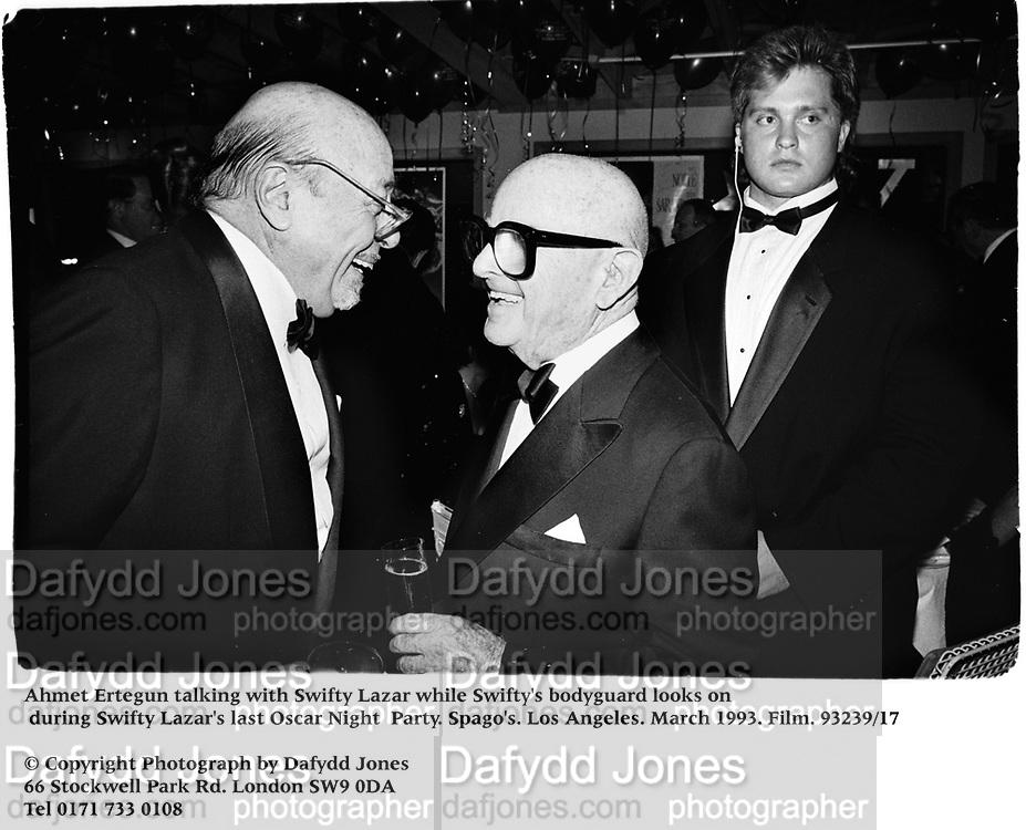 Ahmet Ertegun talking with Swifty Lazar while Swifty's bodyguard looks on at Swifty Lazar's last Oscar Night  Party. Spago's. Los Angeles. March 1993. Film. 93239/17<br /><br />© Copyright Photograph by Dafydd Jones<br />66 Stockwell Park Rd. London SW9 0DA<br />Tel 0171 733 0108
