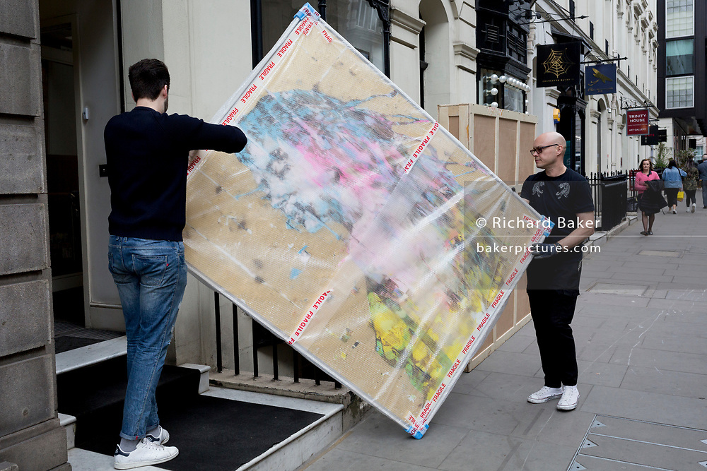 Art removal specialist workmen carry an artwork by Italian artist Marco Grassi, into the Hofer Gallery in Maddox Street, on 30th April 2019, in London, England