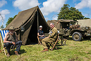 May 30, 2019, Sainte-Mère-Église, Normandy, France. Tourists dressed in military fatigues participates at  reenactments of military deeds from 1944. The 75th anniversary of D-Day and Battle of Normandy commemoration is a tourist attraction.   <br /> 30 Mai 2019, Sainte-Mère-Église, Normandie, France.  Des touristes vêtus de treillis militaires participent à la reconstitution d'actes militaires de 1944.