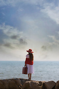 a girl in a white dress with red sunhat, suitcase and shawl is standing on rocks at the sea
