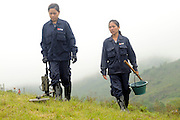 "Mines Advisory Group, Technicians, Sia Thorthongyer, age 19 (left) and Vonekham Dalavong, age 29 (right), use a metal detector and shovel to uncover live bombs hidden in the soil.  Sia and Vonekham said, ""The first time we found a bomb we were afraid.  But we have good training and team work.  We have found many bombs, now it is just normal.  But, if we see a snake - we drop everything and run!"" ..Laos was part of a ""Secret War"", waged within its borders primarily by the USA and North Vietnam.  Many left over weapons supplied by China and Russia continue to kill.  However, between 90 and 270 million fist size cluster bombs were dropped on Laos by the USA, with a failure rate up to 30%.  Millions of live cluster bombs still contaminate large areas of Laos causing death and injury..The US Military dropped approximately 2 million tons of bombs on Laos making it, per capita, the most heavily bombed country in the world.   ..The women of Mines Advisory Group (MAG) work everyday under dangerous conditions removing unexploded ordinance (UXO) from fields and villages...***All photographs of MAG's work must include (either on the photo or right next to it) the credit as follows:  Mine clearance by MAG (Reg. charity)***."