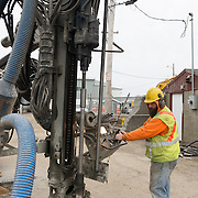Gloucester, MA USA April 14, 2015. A worker drills holes in Commercial Street to support the installation of new water and utility lines.