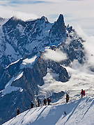 Beneath Dent du Geant in the Mont Blanc massif, helmeted climbers descend from spectacular Aiguille du Midi (12,600 feet), a station on the téléphérique (cable car, aerial tramway) from Chamonix, France, the Alps, Europe.