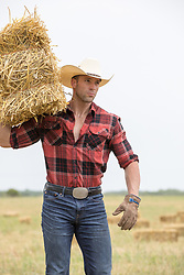 hot cowboy with a hay bale on his shoulder