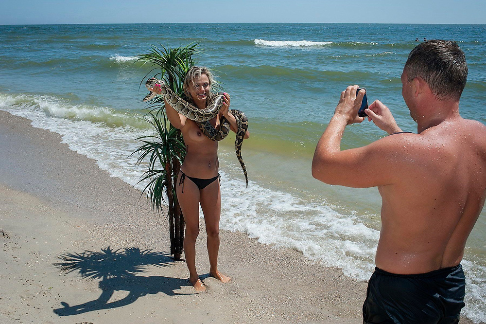 A female tourist, holding a rented snake, poses for a photograph on a beach in front of a plastic palm tree in the cheap Black Sea resort destination of Zatoka, Ukraine