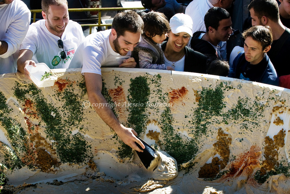 A giant serving of hummus weighting 4,093.5 kilos is seen resting on a six-meters (20 foot) satellite dish while attempting to break a new world record in the Arab Israeli village of Abu Gosh on January 8, 2010. Fifty chefs in the Arab-Israeli village of Abu Ghosh mashed up over four tonnes of hummus, beating the Guinness World Record set in Lebanon just months ago. The weight is about twice as much as the previous record set in October in neighbouring Lebanon, Israel's political and culinary rival..© ALESSIO ROMENZI