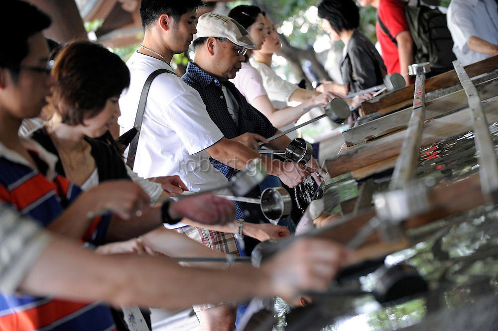 Pilgrims drink and wash their hands at a fountain prior to prayer during events to commemorate the end of World War II  at Yasukuni Shrine in Tokyo, Japan on 15 Aug. 2008. Wartime prime minister Hideki Tojo - who ordered the attack on Peal Harbor and was charged and hanged as a war criminal after World War II, is enshrined inside the controversial Yasukuni Shrine together with 13 other convicted war criminals, a fact that still angers citizens in China and South Korea, both of which fell vicim to Japan's wartime activities. Aug 15. is the anniversary of Japan's surrender in World War II and 100s of thousands of pilgrims from around the country visit the shrine...Photographer: Robert Gilhooly