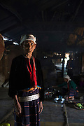 A women who is a member of a sub-group of the Palaung ethnic minority stands inside her family's communal house. The tribe is famous for the silver bands un-married girls wear around their waist, the number depending on the wealth of their family. Once they are married most are removed leaving only a few remaining.