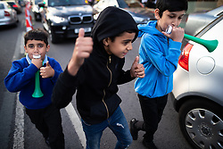 © Licensed to London News Pictures. 15/06/2018. Manchester, UK. Boys run between cars in the street blowing on vuvuzelas . People celebrate Eid-ul-Fitr , the end of a month of fasting during Ramadan , in Rusholme in Manchester . Photo credit: Joel Goodman/LNP