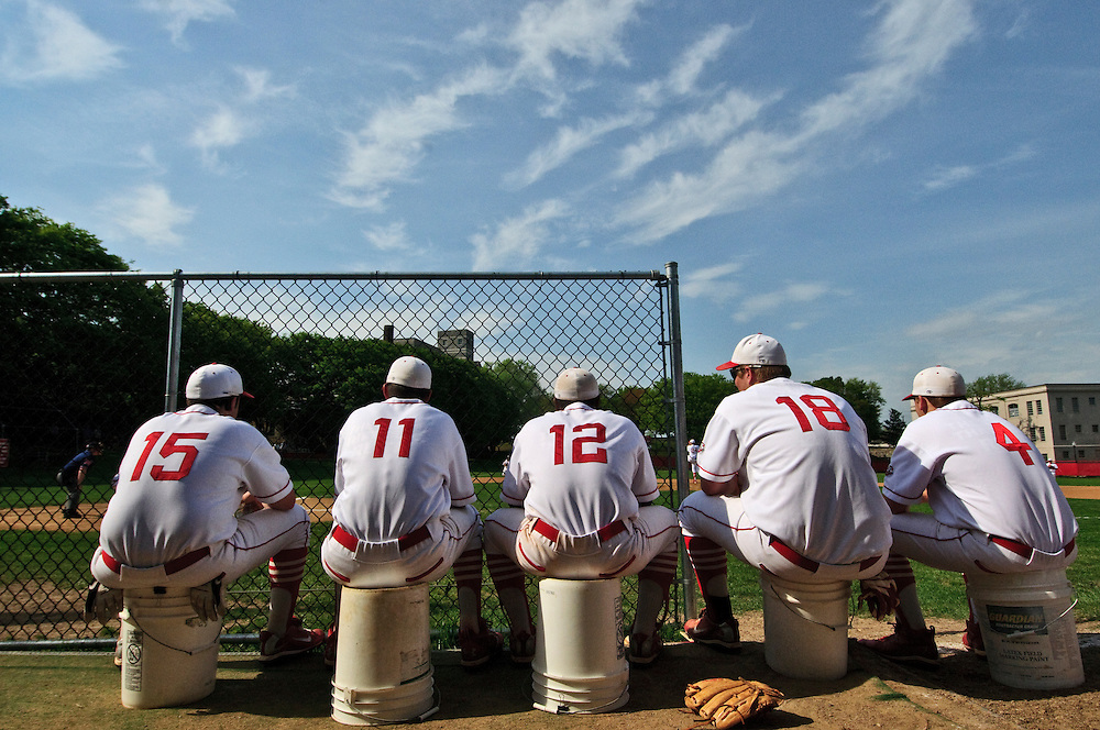 """(photo by Matt Roth).Friday, April 16, 2010.Assignment ID: 30095633A..Cardinal Gibbons players (L-R) Kevin Howley, senior, Frank DiVinlenzo, senior, Ryan Ellis, senior, Alex Kurth, junior, and Garrett Sites, junior, watch the first inning play against St. Paul's School atop buckets..The Archdiocese of Baltimore announced thirteen Catholic Schools will close at the school year's end, including Cardinal Gibbons High School. The site, formerly known as St. Mary's Industrial School, a school for """"wayward boys,"""" was where Babe Ruth played while in high school. The shutting has left the baseball diamond's future susceptible to sale and development."""