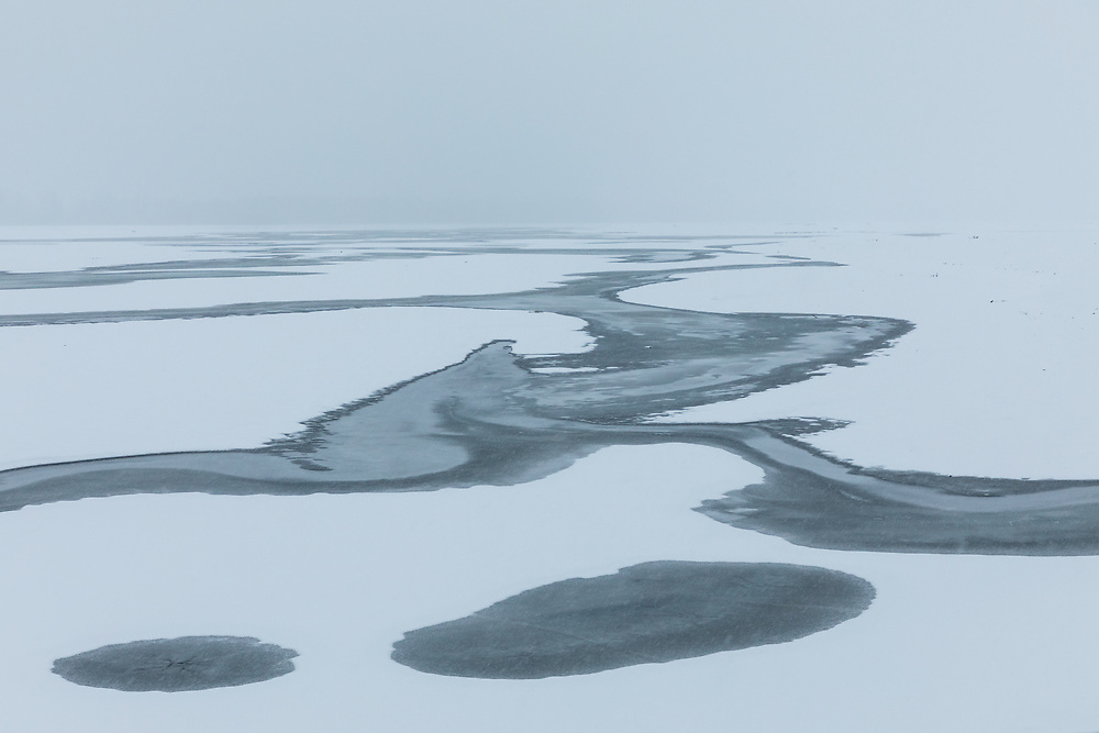 Open water on the Chilkat River creates a winter abstract in Southeast Alaska. Morning.