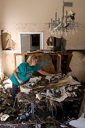 08 Sept 2005.  New Orleans, Louisiana. Hurricane Katrina aftermath. <br /> Venetian Isles in East New Orleans, where the tidal surge washed over the land and devastated homes and property. Peggy Lala struggles to save personal effects from her mud filled flood ravaged home.<br /> Photo; ©Charlie Varley/varleypix.com
