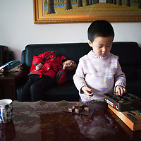 Beijing, March 11 : Tian Peng, 15, lies on the sofa while his little brother Tian Ye, 3, plays in the apartment.<br />