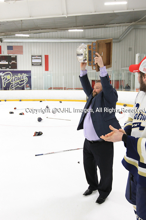 TORONTO, ON - Apr 22, 2015 : Ontario Junior Hockey League game action between the Toronto Patriots and the Kingston Voyageurs. Game seven of the Buckland Cup Championship Series. Jason Fortier Head Coach of the Toronto Patriots raises the Cup.<br /> (Photo by Tim Bates / OJHL Images)