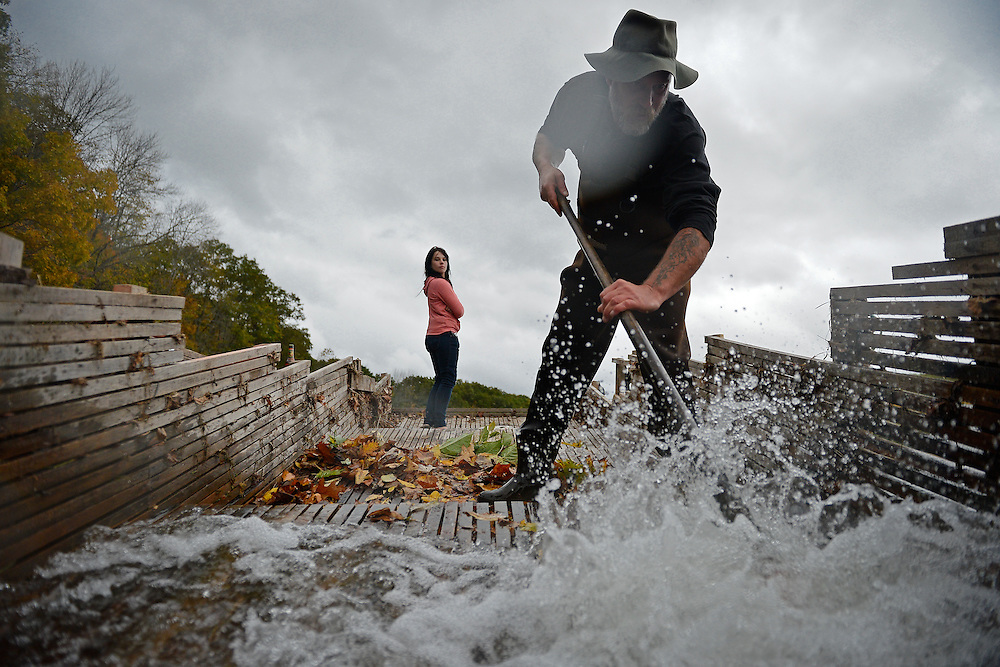 Narrowsburg resident Tommie Campfield clears autumn leaves from his eel catching pen in the center of the Delaware River as his daughter Cat looks on. The river eels that are caught are cooked and sold by Tommie to supplement his income.