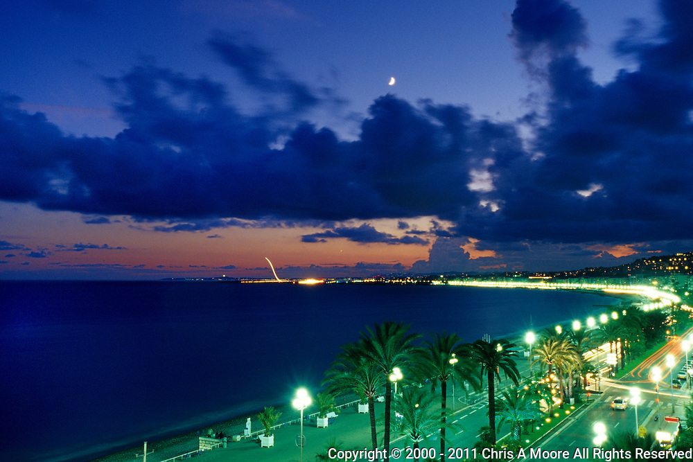 An aircraft takes off from the airport in Nice, France at dusk.  People are sitting along the well lighted Promenade des Anglais enjoying the warm evening.  Traces of cars can be seen by their lights on the roadway.  Shot from a balcony at Hotel Negresco.
