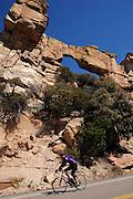 Cyclists make their way past a natural arch on Mount Lemmon, Santa Catalina Mountains, Coronado National Forest, Sonoran Desert, Tucson, Arizona, USA.