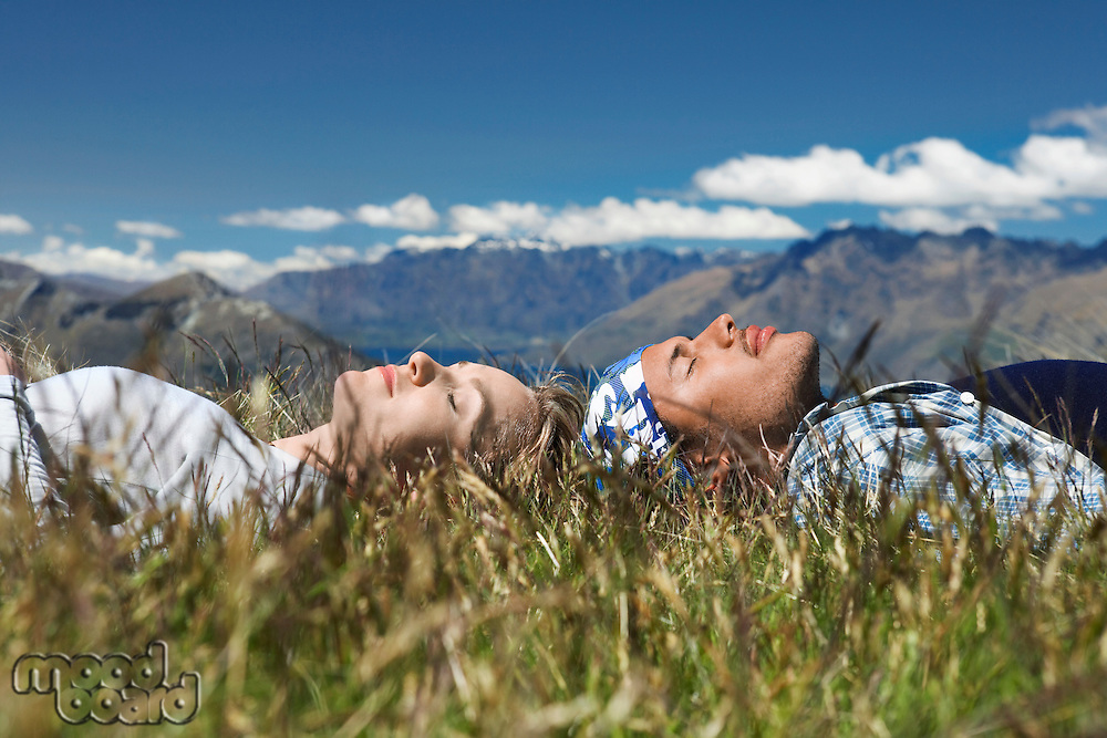 Man and woman lying in field overlooking hills