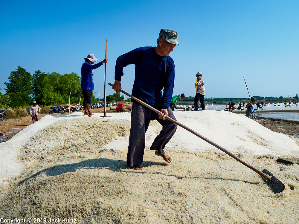 20 FEBRUARY 2019 - BAN LAEM, PHETCHABURI, THAILAND: A worker rakes a mound of salt on one of the first days of the 2019 salt harvest in Ban Laem, Thailand. Ban Laem's salt fields are expanding because salt harvesters in Samut Sakhon and Samut Songkhram,  which are closer to Bangkok, are moving to Ban Laem as their land is turned into industrial parks.      PHOTO BY JACK KURTZ