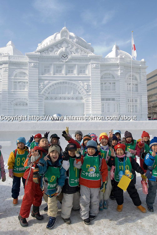 Schoolchildren outside large snow sculpture of building in Odori Park Sapporo during annual snow sculpture festival in Japan