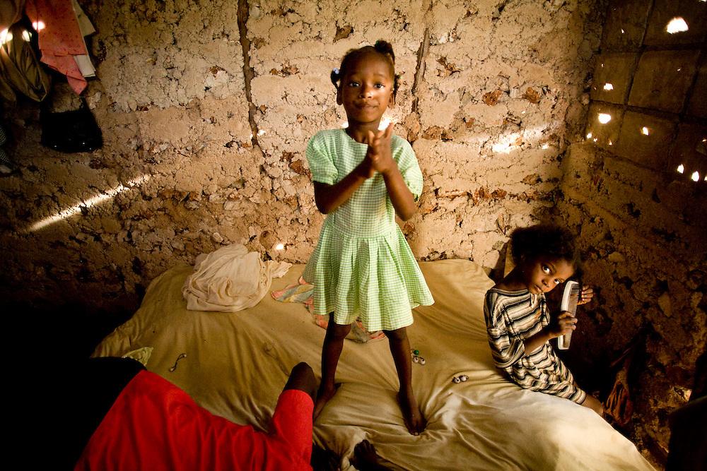 Legime Merilas helps her daughter Ken Chi Love get ready for school in Plenn Lasous, La Gonave, Haiti. Photo by Ben Depp