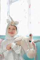 Portrait of young girl (5-6) in unicorn costume holding toy horse smiling indoors