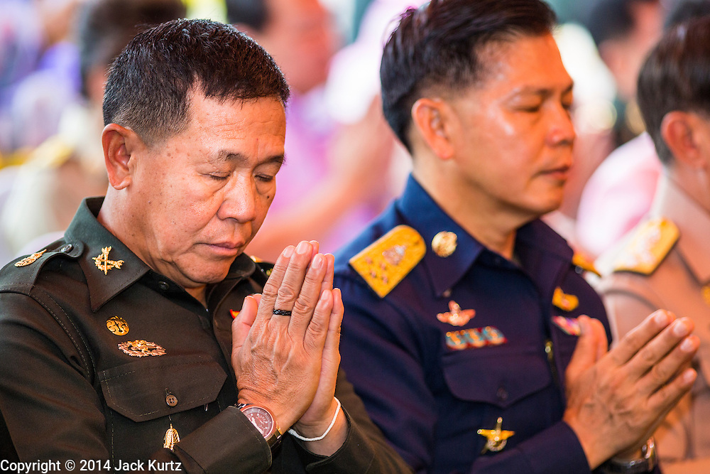 "22 JULY 2014 - BANGKOK, THAILAND: Thai Army and Air Force officers representing the ruling junta pray during a religious service at Sanam Luang. Hundreds of Thai military officers and civil servants attended a Buddhist chanting service and merit making ceremony to mark the 2nd month anniversary of the May 22 coup that deposed the elected civilian government and ended nearly six months of sometimes violent anti-government protests. The ruling junta said the ceremonies Tuesday were the kickoff to a ""Festival to Bring Back Happiness of the People of the Nation."" There will be free concerts, historical pageants and movies at Sanam Luang, a large parade ground near the Ministry of Defense in Bangkok.    PHOTO BY JACK KURTZ"