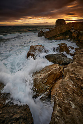 Pulpit Rock at sunset under a stormy sky. The rising tide causes waves to break over the foreground rocks. <br /> <br /> Portland Bill in Dorset, England