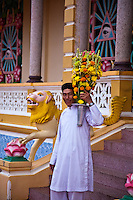 Worshipper bringing flowers out of the Holy See in Tay Ninh.