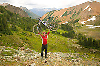 A mountain biker, with bike held over his head, proudly stakes his claim, riding amongst the beautiful Southern Chilcotin Mountains.  Goldbridge, Southern Chilcotin Mountains, British Columbia, Canada.