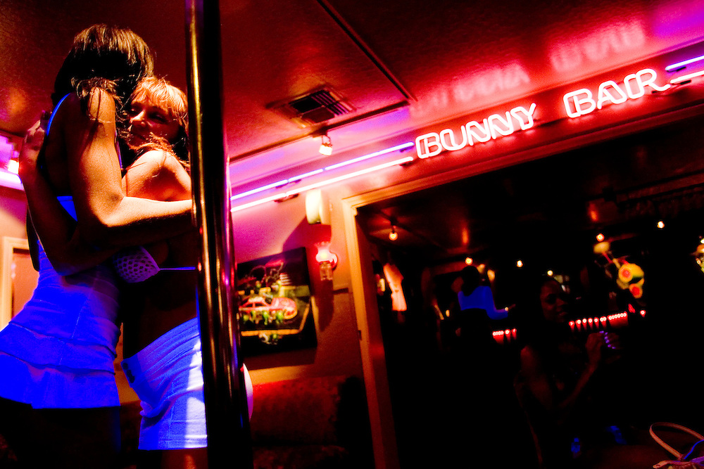 """Sex workers, from left, Nina Nicole and Alexis Fire embrace in the parlor of Moonlite Bunny Ranch brothel in Mound House, NV on Friday, July 28, 2006...The Moonlite Bunny Ranch brothel in Mound House, Nevada - just a few miles from the state capital in Carson City - first opened in 1955. The Ranch is a legal, licensed brothel owned by Dennis Hof. It's featured in the HBO series """"Cathouse."""" the"""