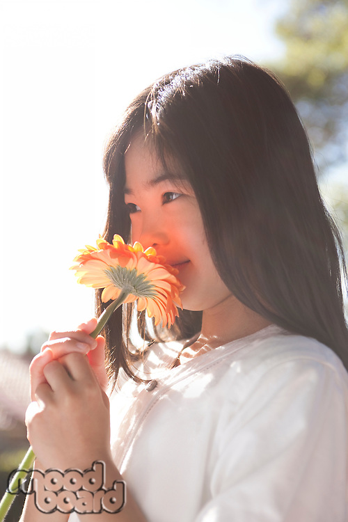 Asian girl smelling flower scent
