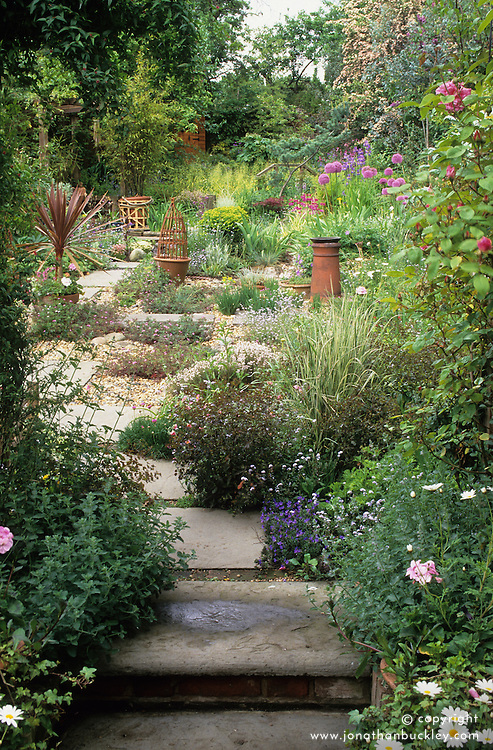 Narrow garden with paved path leading up through gravel area to wilder patch at the rear
