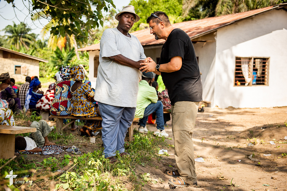 The Rev. Doug Thompson, carrier missionary to Sierra Leone, prays with a man waiting for treatment on the first day of the LCMS Mercy Medical Team on Monday, May 7, 2018, in the Yardu village outside Koidu, Sierra Leone, West Africa. LCMS Communications/Erik M. Lunsford