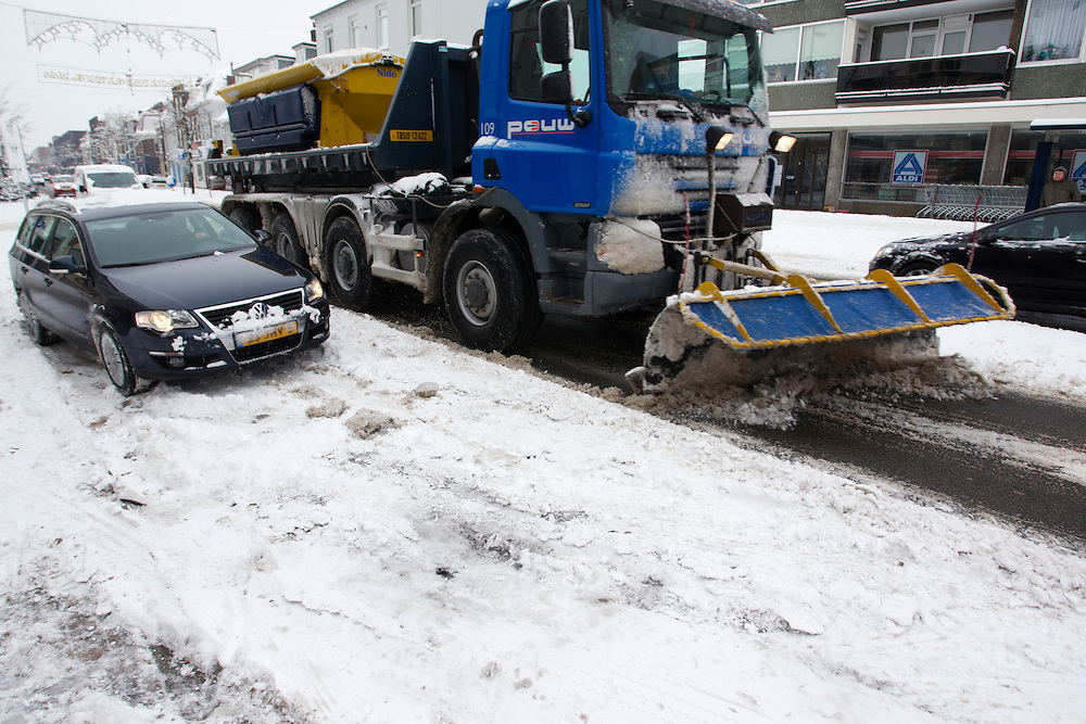 Een sneeuwschuiver passeert een auto die vast zit op de Amsterdamsestraatweg in Utrecht. De hevige sneeuwval levert de nodige problemen op in Nederland.<br /> <br /> A plow is passing a car which is stuck at the Amsterdamsestraatweg in Utrecht. Due to the heavy snowfall this winter traffic is having a lot of problems.