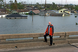 29 August, 2005. New Orleans, Louisiana.<br /> Hurricane Katrina hits New Orleans. Ryan Parry of London's Daily Mirror stands on the elevated section of I-10, bearing witness to the destruction of Katrina.<br /> Photo; Charlie Varley.