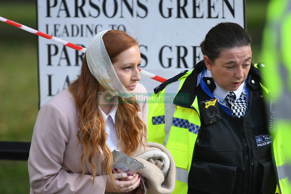 """An injured woman is assisted by a police officer close to Parsons Green station in west London after Scotland Yard declared a terrorist incident following a blast sent a """"fireball"""" and a """"wall of flame"""" through a packed London Underground train."""