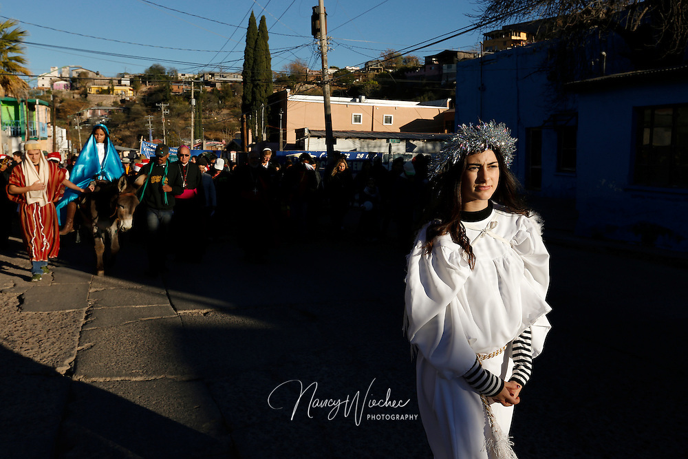 "Dressed as an angel, Zuhaila Parra leads a procession along a street in Nogales, Sonora, Dec. 20. Kino Teens from Salpointe and Lourdes Catholic high schools in Nogales, Arizona, took part in the bi-national ""posada,"" recalling Mary and Joseph's search for shelter before the birth of Christ. The annual event held by the Kino Border Initiative and Dioceses Without Borders reflected on the struggles of migrants and migrant families. (CNS photo/Nancy Wiechec)"