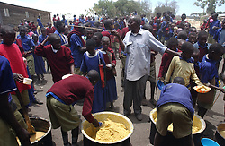 Children wait in line to be fed lunch at the Endolin Primary school in Ngornogoro District in Tanzania September 29, 2003. The Masai were thrown out of the Crater in 1972 and struggle to hang onto the lands they live on now because of increasing pressure from conservationists. (Ami Vitale)