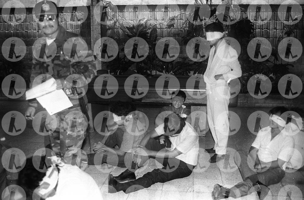 Un miembro de la Policia Nacional toma datos a estudiantes de la Universidad de El Salvador que fueron capturados durante una marcha para exigir un presupuesto para la universidad de El Salvador 13 de Agosto de 1988.(IL Photo).