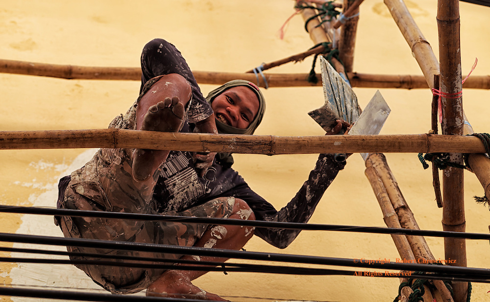A young male construction worker casts out a happy smile as he rests perched on bamboo scaffolding right over top of hydro-electric wiring, in Bangkok Thailand.<br /> <br /> The man is covered with protective clothing, plaster and holds a couple of hand tools.
