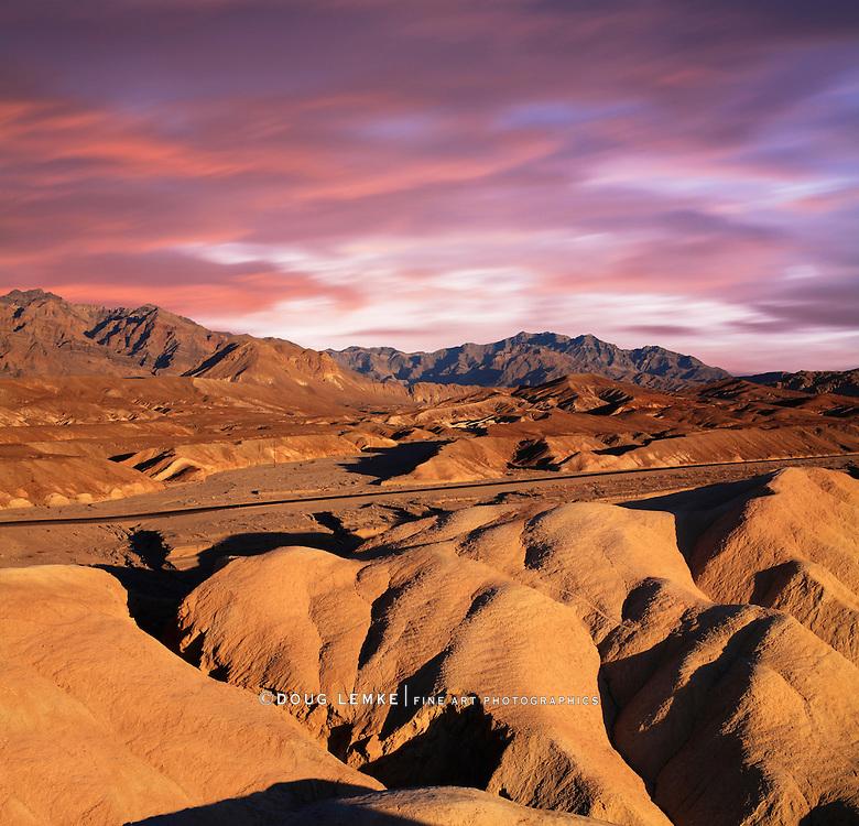A Desert Highway Traversing The Bizarre Mars-Like Landscape Of Heavily Eroded Ridges At Zabriskie Point, Death Valley National Park, California, USA